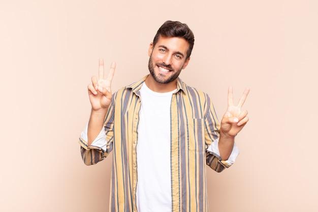 若い男は笑顔で幸せそうに見え、友好的で満足し、両手で勝利または平和を身振りで示す