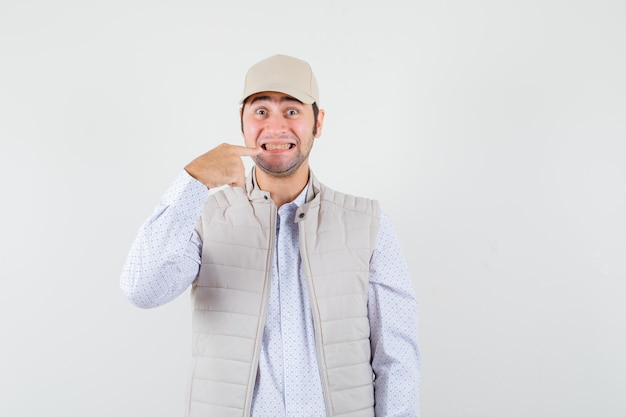웃 고 베이지 색 재킷과 모자에 검지 손가락으로 입을 가리키고 행복을 찾는 젊은 남자. 전면보기.