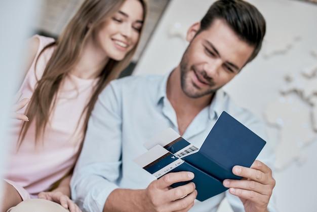 若い男が笑顔でビザ付きのチケットパスポートを復活させる