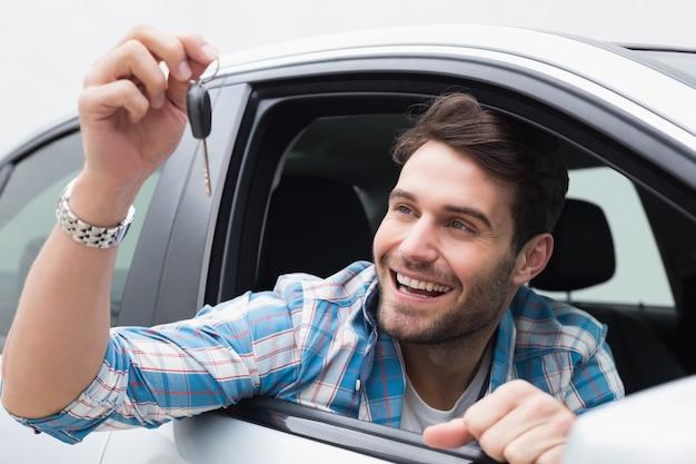 若い男は笑顔とキーを表示