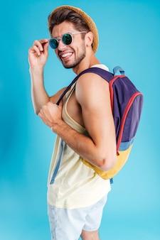 모자, 가방, 선글라스를 쓰고 웃고 있는 청년
