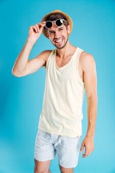 Молодой человек улыбается и носит шляпу и солнцезащитные очки