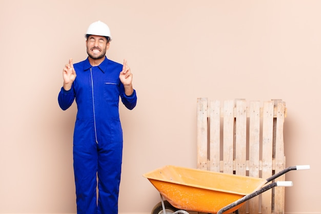 Young man smiling and anxiously crossing both fingers, feeling worried and wishing or hoping for good luck construction concept