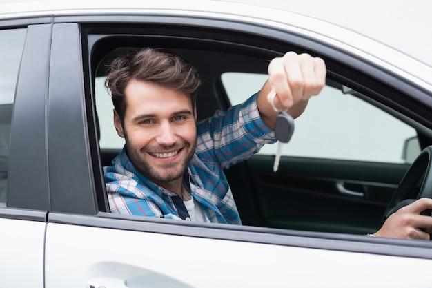 彼の車の中に鍵を見せてカメラで笑っている若い男