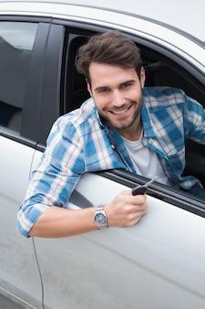 Young man smiling at camera showing key