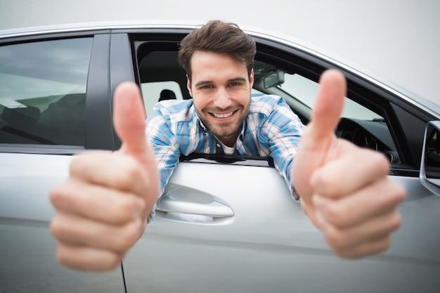 Young man smiling at camera showing thumbs up