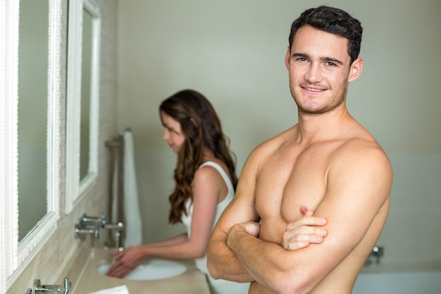 Young man smiling at camera and woman washing her hands behind him
