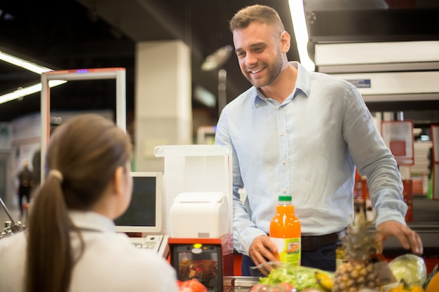 Young man smiling to cashier in supermarket