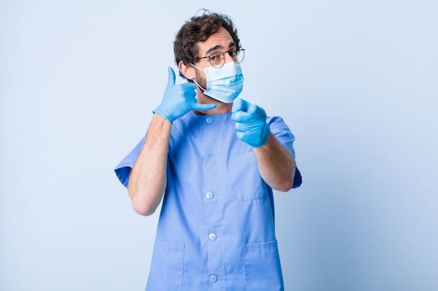 若い男が元気に笑って、後でジェスチャーをかけて電話で話しているときにカメラを指しています。コロナウイルスの概念