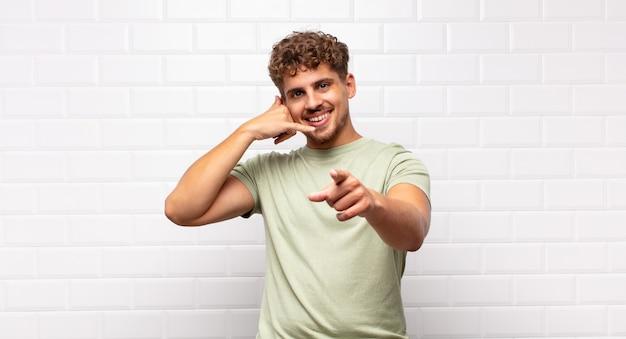 Молодой человек весело улыбается и указывает на камеру, звоня вам позже жестом, разговаривая по телефону