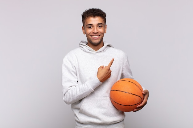 若い男は元気に笑って、幸せを感じて、横と上を指して、コピースペースにオブジェクトを示しています。バスケットコンセプト