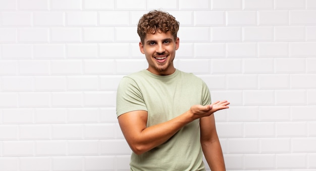 Young man smiling cheerfully, feeling happy and showing a concept in copy space with palm of hand