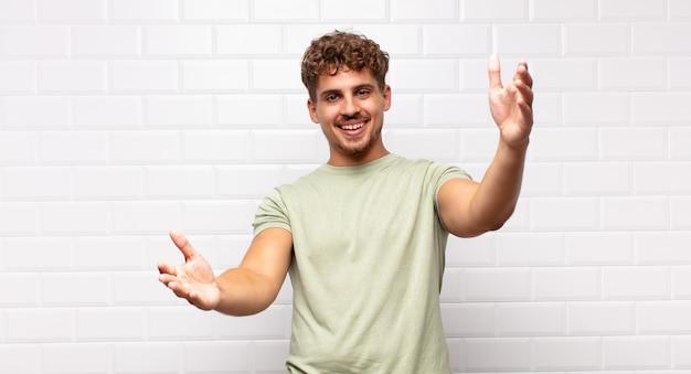 따뜻하고 친절하며 사랑스럽고 환영 포옹을주고 행복하고 사랑스러운 느낌을주는 쾌활하게 웃는 젊은 남자