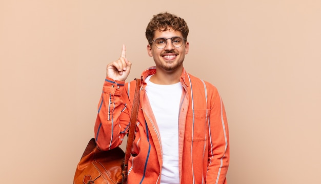 Young man smiling cheerfully and happily, pointing upwards with one hand to copy space. student concept