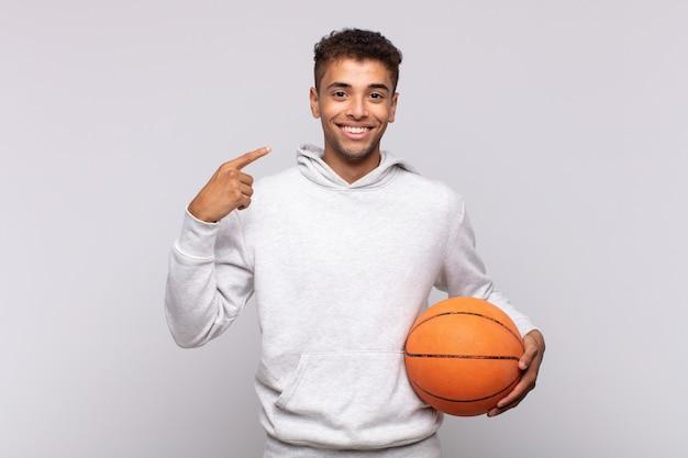 自信を持って笑顔の若い男は、自分の広い笑顔、前向きで、リラックスした、満足のいく態度を指しています。バスケットコンセプト