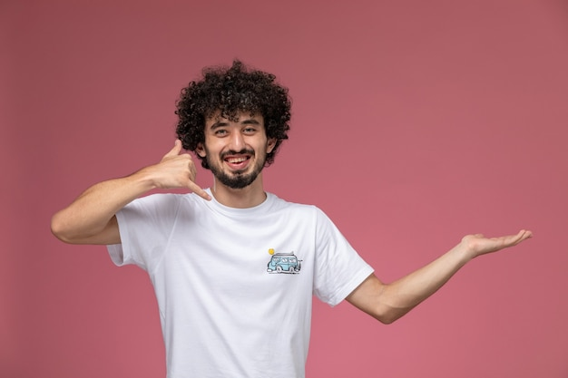 Young man smiling and demonstrating call me gesture
