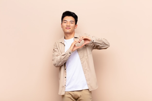 Young man smiling and feeling happy, cute, romantic and in love, making heart shape with both hands over wall