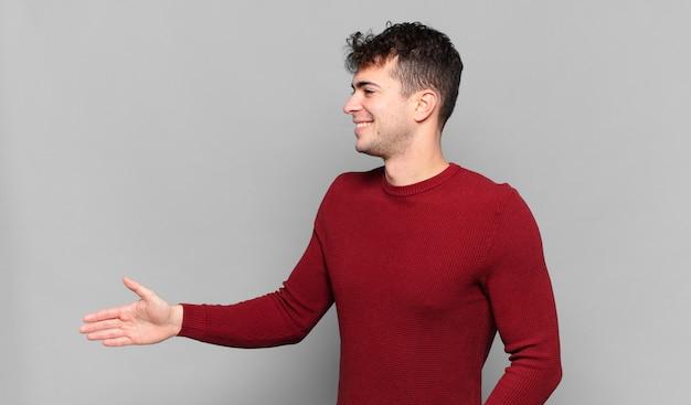 笑顔、挨拶、握手を提供して成功した取引、協力の概念を閉じる若い男