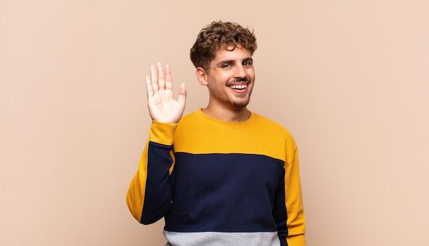 孤立した手を振って、楽しく元気に笑っている若い男