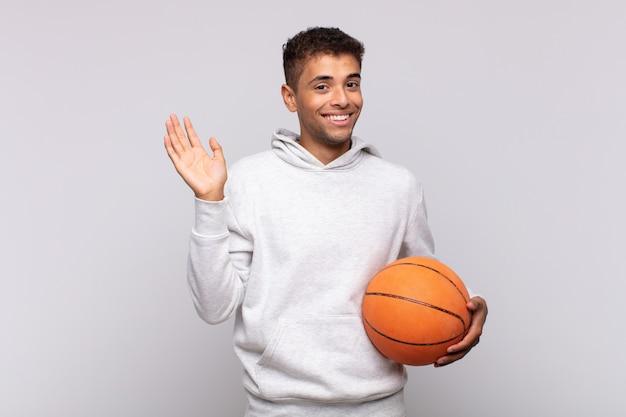 若い男は幸せにそして元気に笑って、手を振って、あなたを歓迎して挨拶するか、さようならを言います。バスケットコンセプト