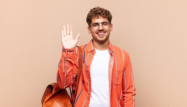 若い男は幸せにそして元気に笑って、手を振って、あなたを歓迎して挨拶するか、さようならを言います。学生の概念