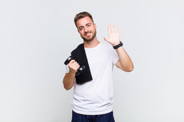 Молодой человек счастливо и весело улыбается, машет рукой, приветствует и приветствует вас или прощается
