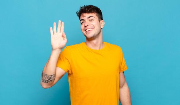 若い男は幸せにそして元気に笑って、手を振って、あなたを歓迎して挨拶するか、さようならを言っています