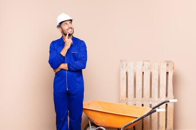幸せに笑って、空想にふけるか、または疑って、側面の建設コンセプトに目を向ける若い男