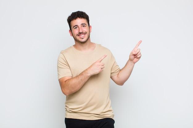 젊은 남자가 행복하게 웃고 복사 공간에 개체를 보여주는 양손으로 측면과 위쪽을 가리키는