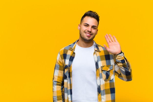 Young  man smiling happily and cheerfully, waving hand, welcoming and greeting you, or saying goodbye against orange wall