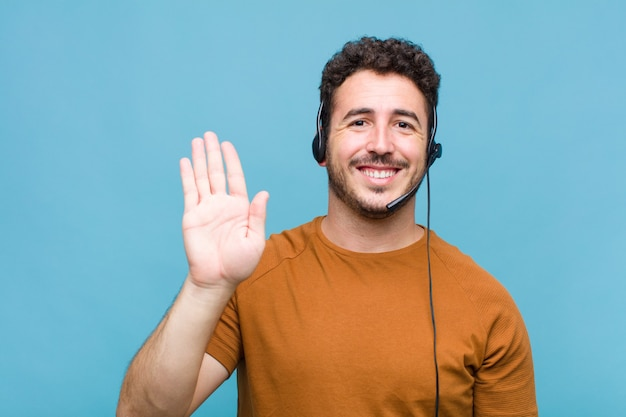 Young man smiling happily and cheerfully, waving hand, welcoming and greeting you, or saying goodbye