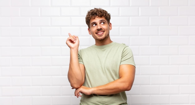Young man smiling happily and looking sideways, wondering, thinking or having an idea