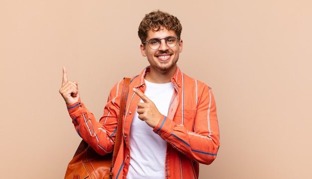 Young man smiling happily and pointing to side and upwards with both hands showing object in copy space