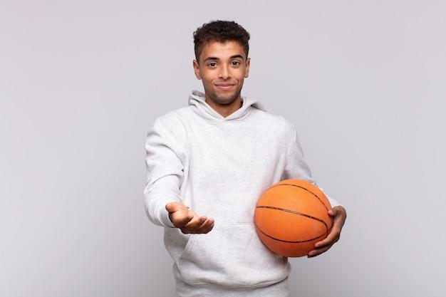 フレンドリーで自信に満ちた前向きな表情で幸せそうに笑っている若い男は、オブジェクトやコンセプトを提供し、示しています。バスケットコンセプト