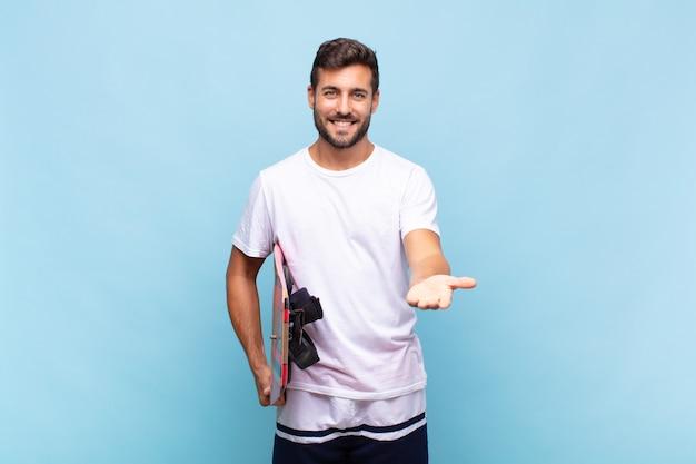 Молодой человек счастливо улыбается, дружелюбно, уверенно, позитивно смотрит, предлагая и показывая объект