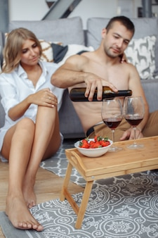 Young man smiling to his gorgeous woman while have romantic dinner and drinking wine