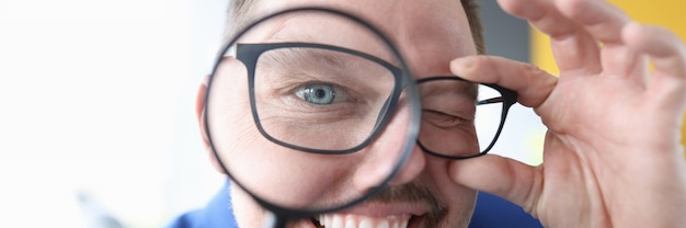 Young man smiling and holding magnifying glass in front of his eyes closeup error  concept