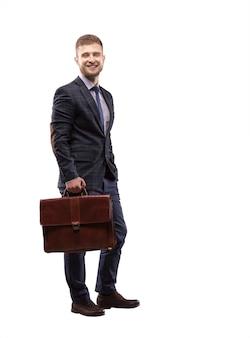Молодой человек улыбается в костюме с портфелем в руках