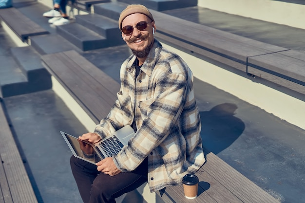 노트북을 손에 들고 야외 해변에 앉아 카메라를 보며 웃고 있는 젊은 남자