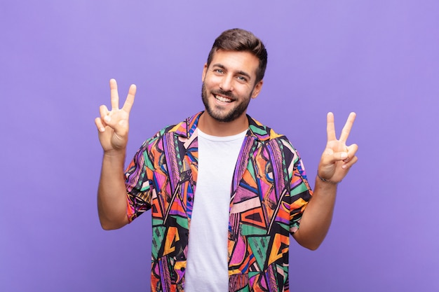Young man smiling and looking happy, friendly and satisfied, gesturing victory or peace with both hands
