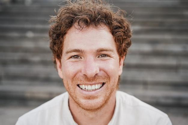 街の屋外で楽しんでいるカメラに微笑んでいる若い男-顔に焦点を当てる