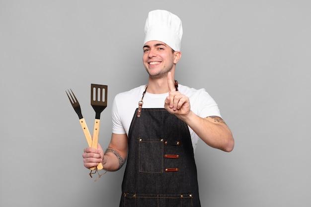 リーダーのように、誇らしげに自信を持って笑顔でナンバーワンのポーズをとる青年