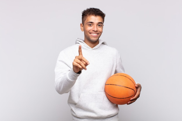 Young man smiling proudly and confidently making number one pose triumphantly, feeling like a leader. basket concept