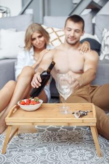 낭만적 인 저녁 식사를하고 발렌타인 데이에 와인을 마시는 동안 그의 화려한 여자에게 웃고있는 젊은 남자