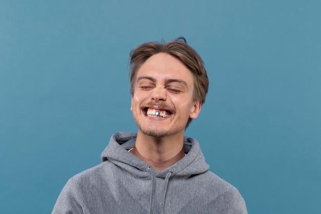 은색 치아를 가지면서 웃고 있는 청년