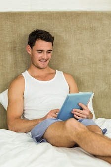 Young man smiling while using digital tablet in bedroom
