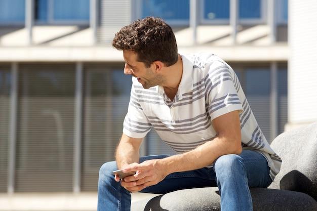 屋外で携帯電話で笑っている若い男