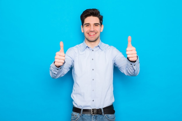 Young man smiling with thumbs up on blue space