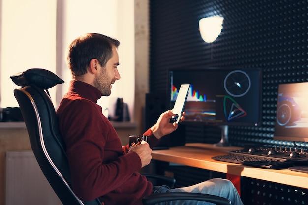 Молодой человек улыбается, работает в студии с помощью смартфона и компьютера. графики на фоне экранов.