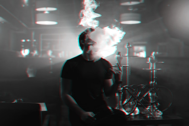 Young man smokes a hookah and lets out a cloud of smoke